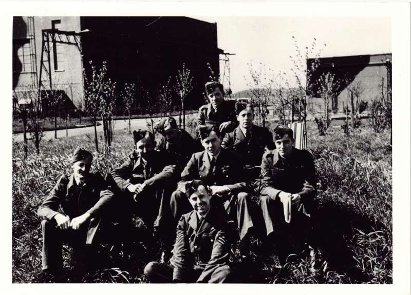 8 men in RAF uniforms sat on the grass at a barracks. Leonard Cheshire in the centre