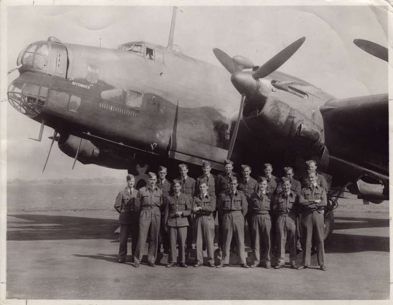 A posed group of 15 men in RAF uniforms in front of a large war plane