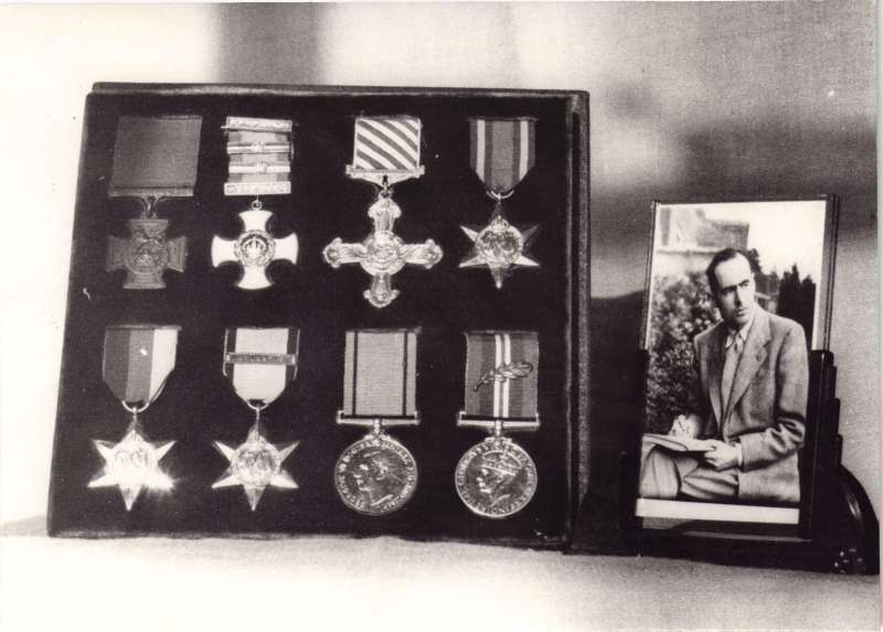 A photo of 8 war medals in a display box alongside a small photo of a young Leonard Cheshire