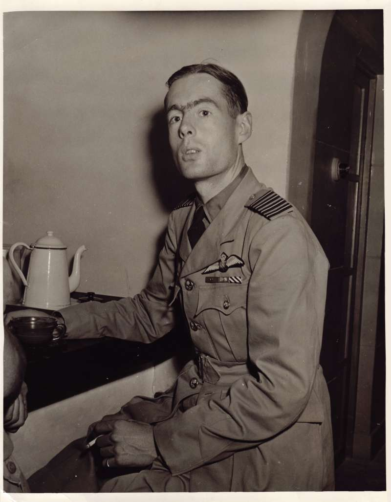 Leonard Cheshire in uniform smoking a cigarette and drinking coffee