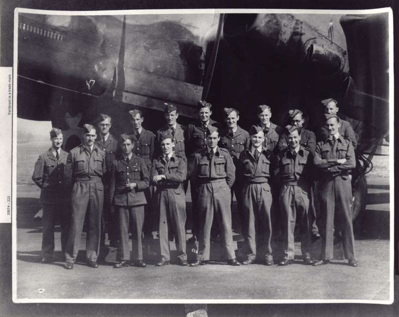 Close up of posed group of 15 men in RAF uniforms in front of a large war plane