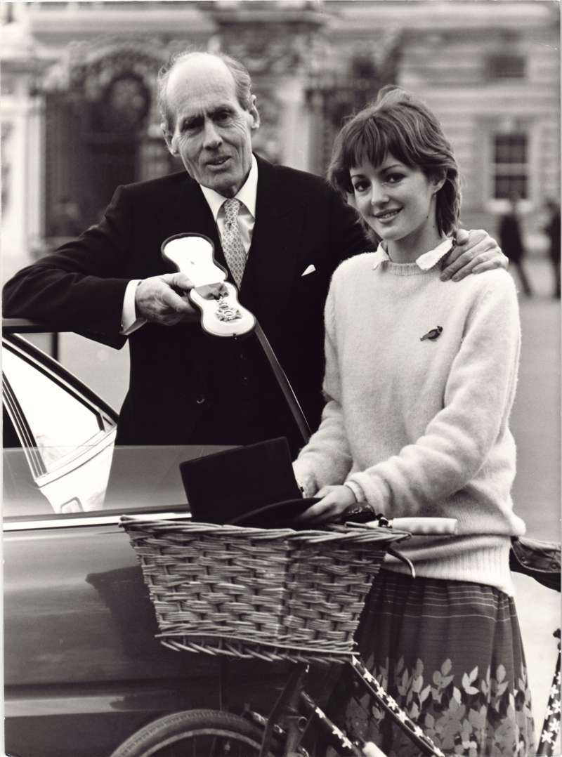 Leonard Cheshire holding his Order of Merit standing with Elizabeth Cheshire next to a bicycle with a basket