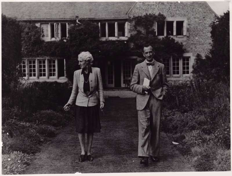 A man and woman walking along a garden path in front of a typical English country cottage