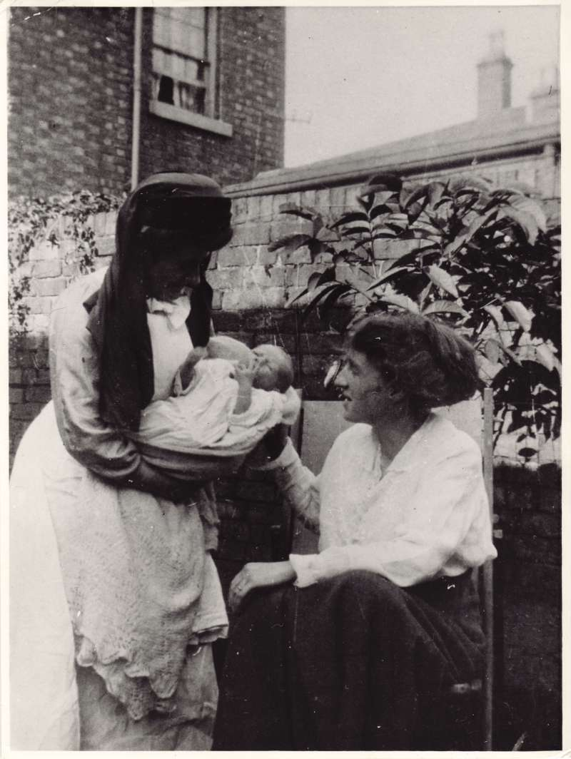 A baby being handed to a woman in a deckchair, sat in a garden