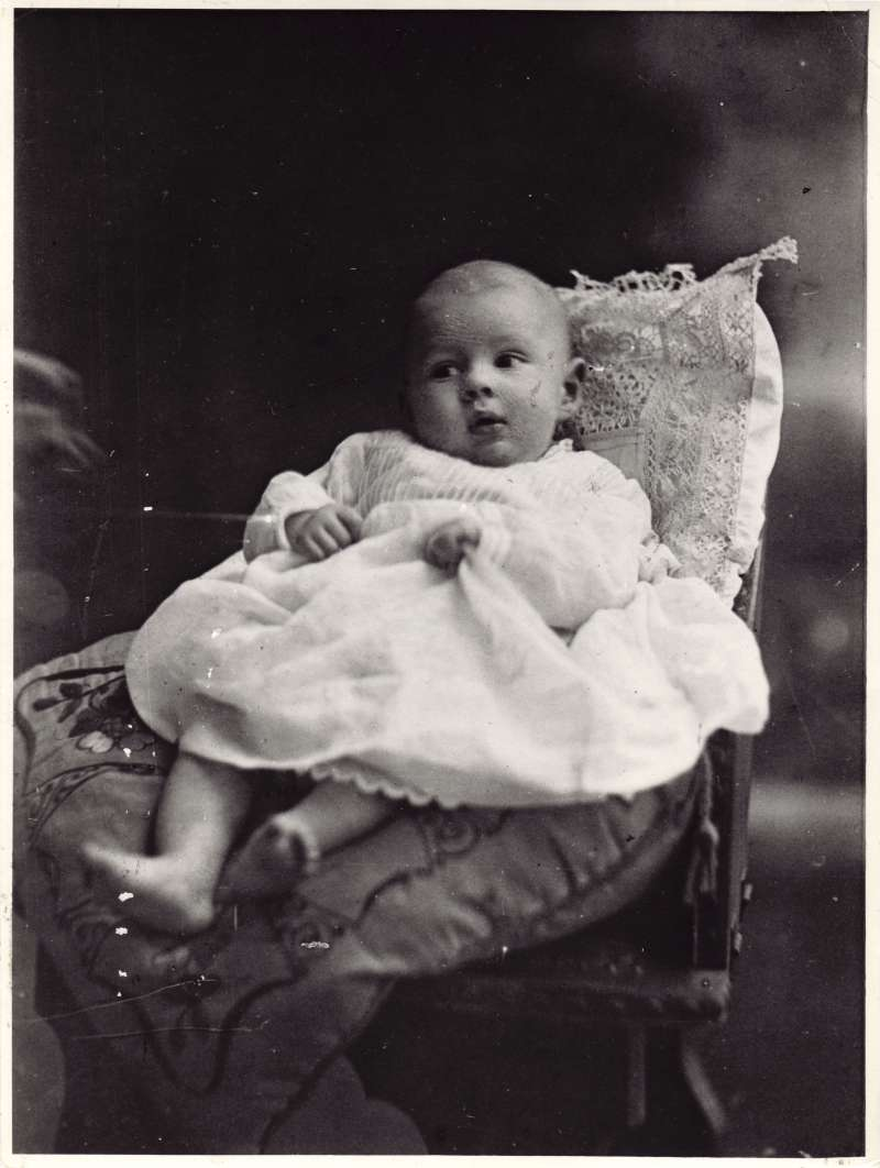 Close up of Leonard Cheshire as a baby, sat on a cushion in a chair