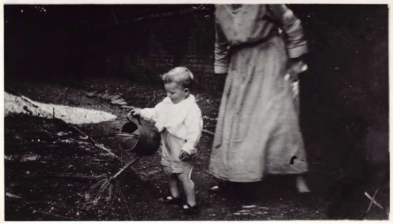 A young Leonard Cheshire using a watering can in the garden, watched by a lady