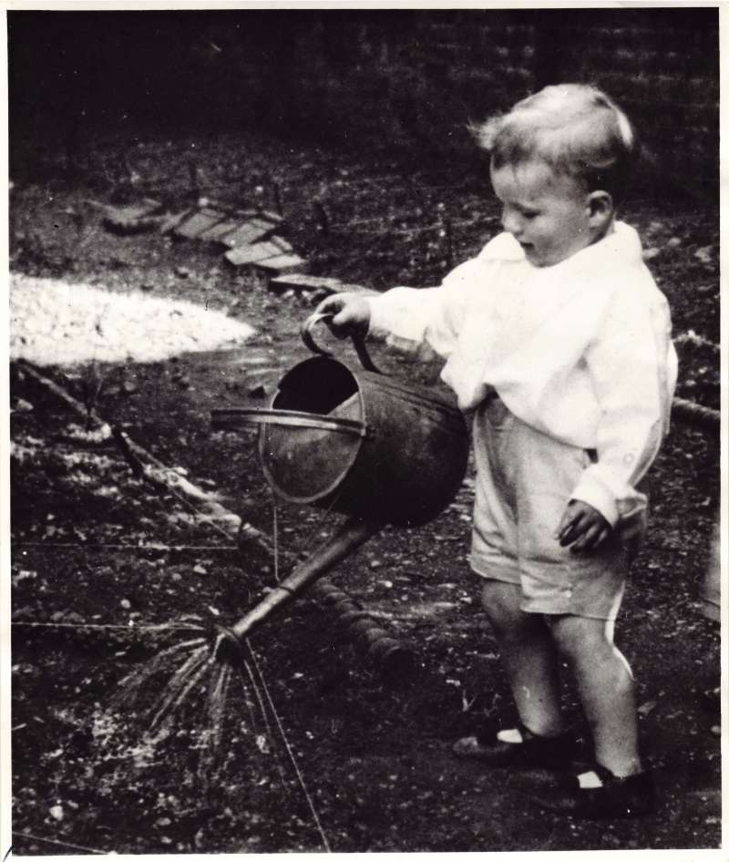 Close up shot of Leonard Cheshire as a toddler using a watering can in the garden