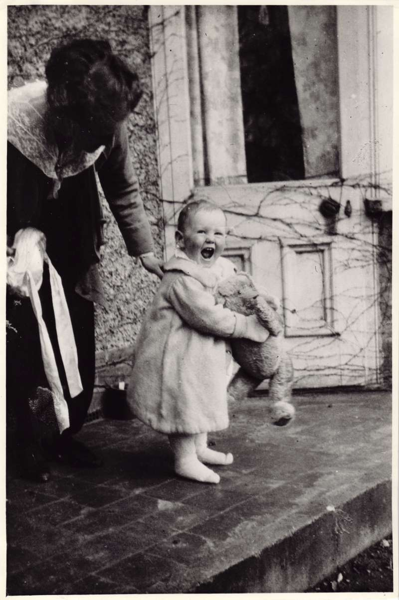 A smiling young Leonard Cheshire holding a teddy bear, being steadied by his mother