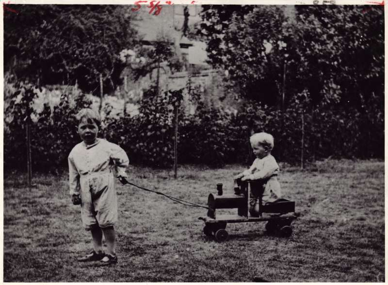 A small boy pulling along a younger boy sat on a pull-along steam train in a garden