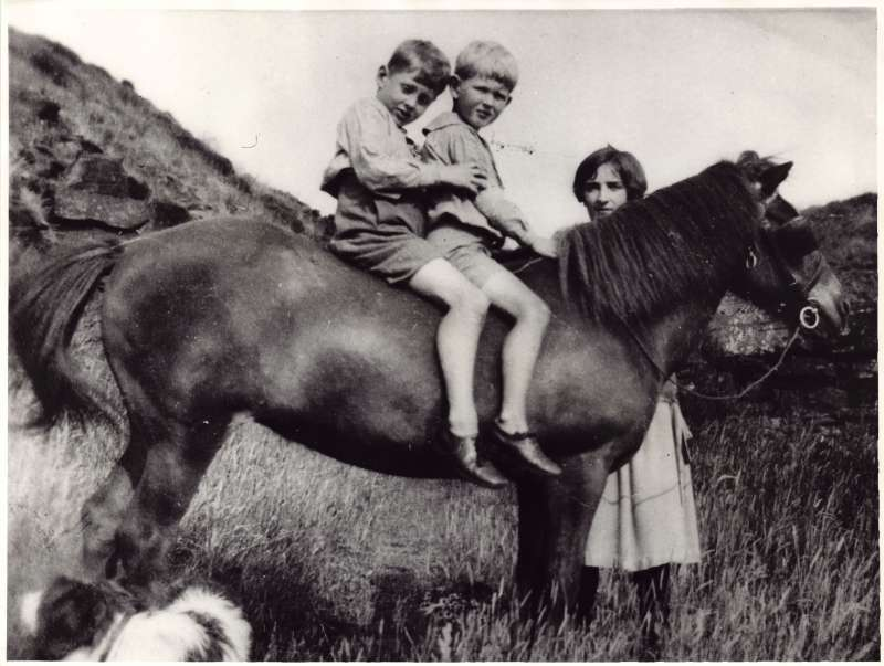 Leonard and Christopher Cheshire as boys riding on a pony with a woman watching on