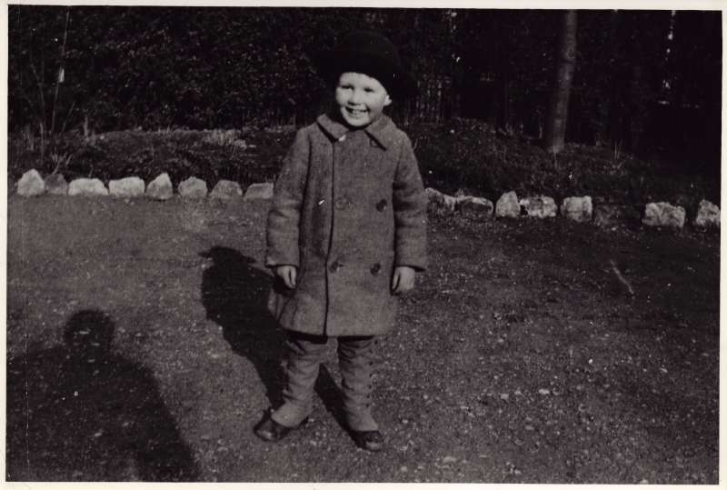 A young Leonard Cheshire wearing a winter coat and hat outside smiling at the camera