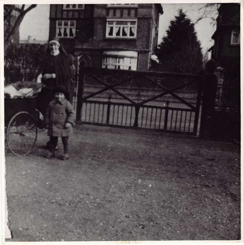 Leonard Cheshire aged about four standing inside a garden gate with a woman pushing a pram
