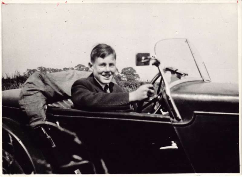 A teenage Leonard Cheshire smiling and driving an open top car