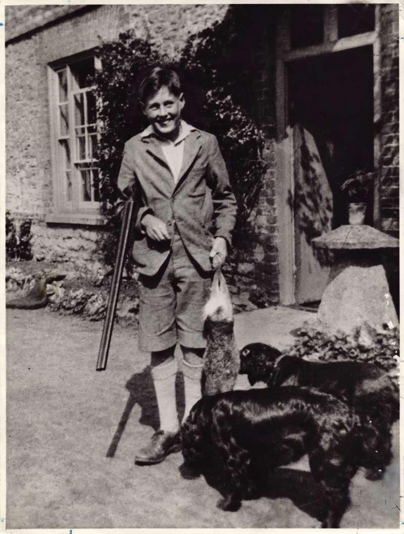 Leonard Cheshire as a young teenager holding a gun and carrying a dead rabbit, with two dogs in the foreground