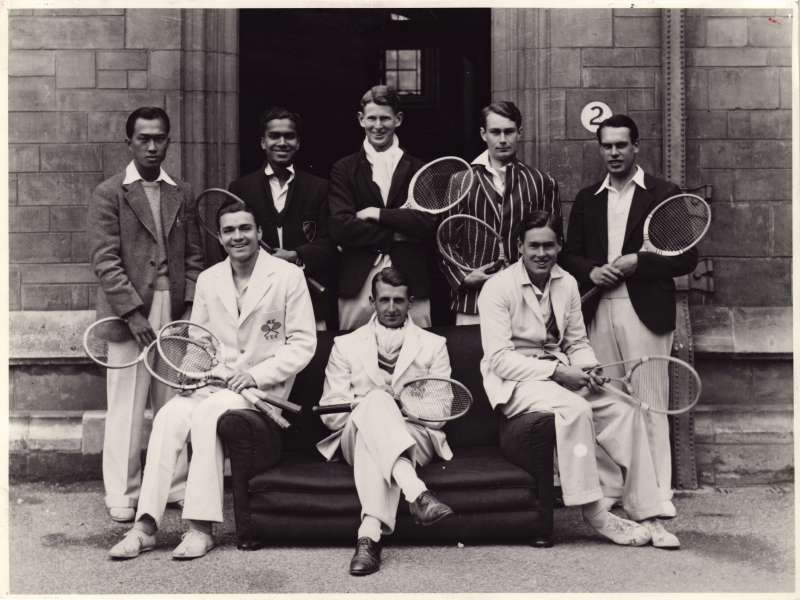 A posed group of young college students holding tennis racquets, some sitting on a sofa