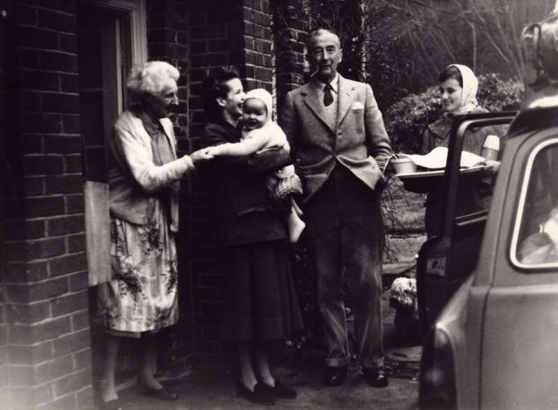 Family shot of Sue Ryder holding a baby Elizabeth with Leonard's parents and another woman near a car