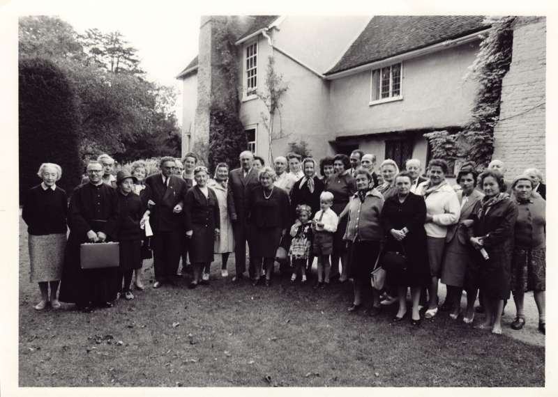 A large group of men and women, with Sue Ryder and the children in front of a house with trees and plants