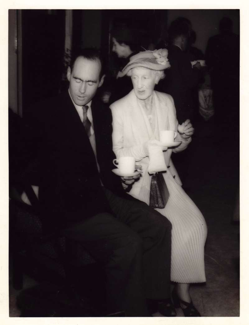 Leonard Cheshire in a suit and his mother in a light dress and hat sat drinking tea at an event