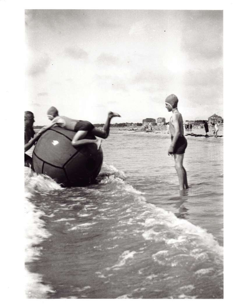 Two young boys wearing swimsuits and swimming caps playing with a giant ball on a beach