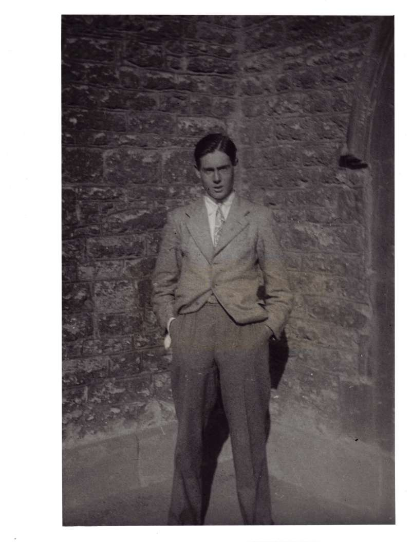 Leonard Cheshire standing with his hands in his pockets outside a stone building posing for the camera