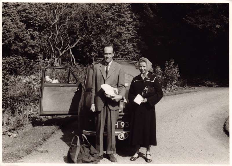 Leonard and Sue standing in front of a small car along a country lane with bags and documents in their hands