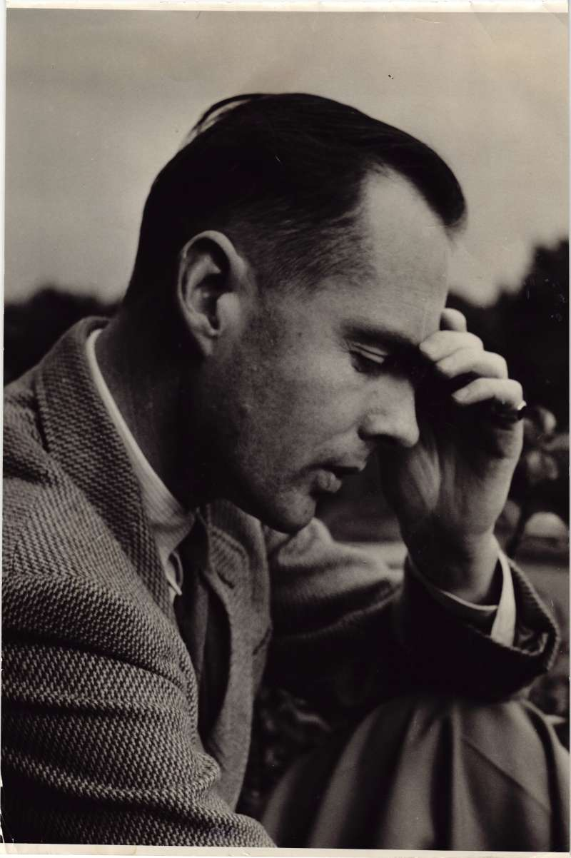 Close up of a side-on shot of Leonard Cheshire sat outside holding one hand to his forehead