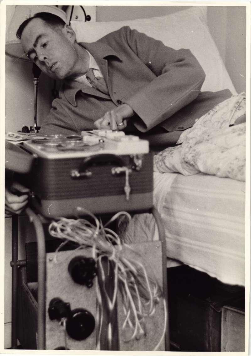 Leonard Cheshire in a hospital bed leaning over to use tape recording equipment