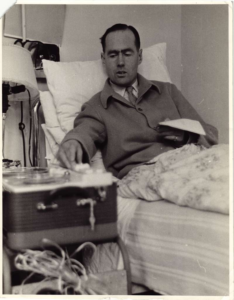 Leonard Cheshire sat up in a hospital bed using tape recording equipment
