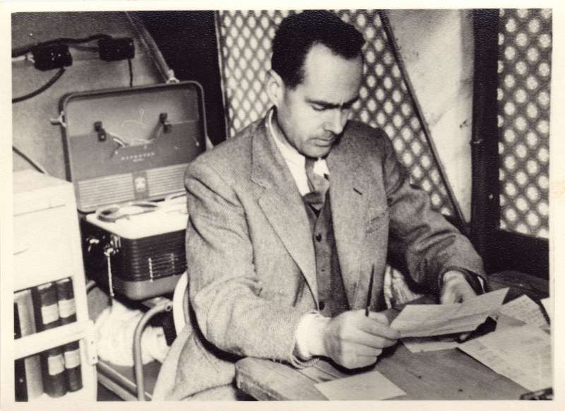 Leonard Cheshire reading documents in a temporary office on a minibus