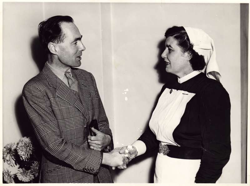 Leonard Cheshire in a striped jacket talking and shaking hands with a woman in a nurse uniform