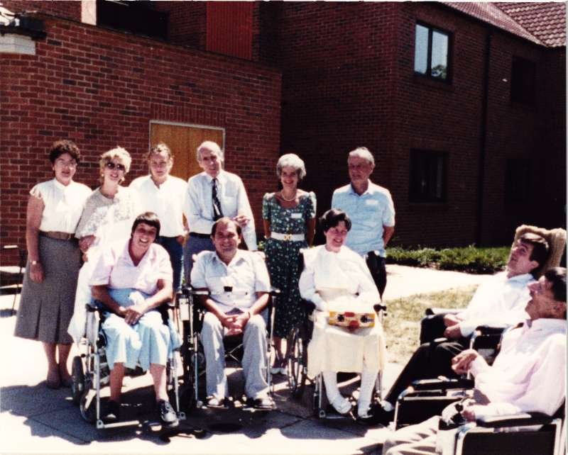 An older Leonard Cheshire with a group of people, some in wheelchairs in front of a brick building