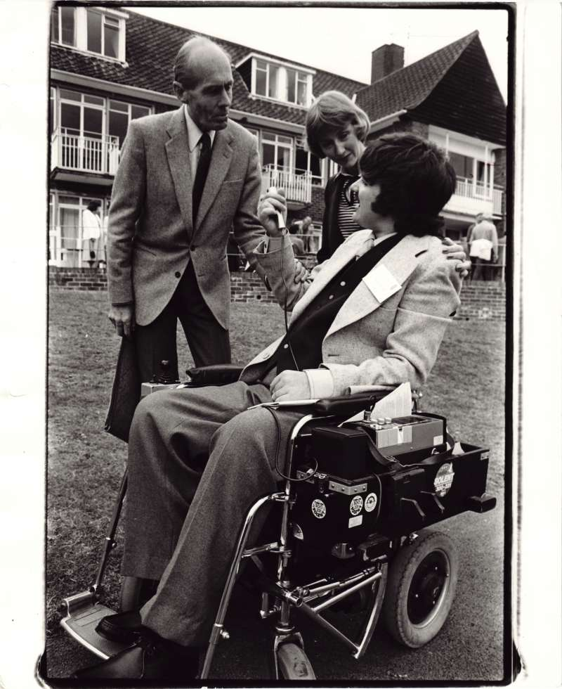 Leonard Cheshire and a woman talking to a man in a wheelchair in the Le Court grounds