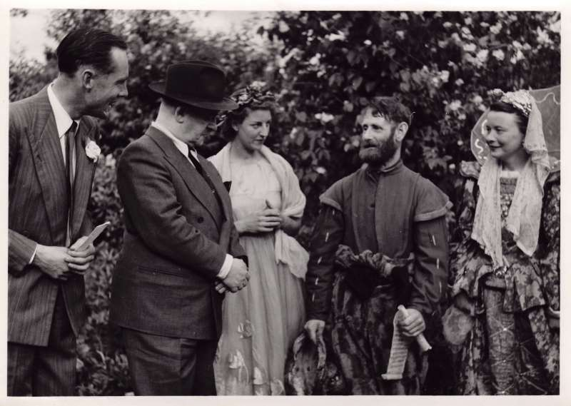 Leonard Cheshire and another man talking with 3 cast members from a theatre production