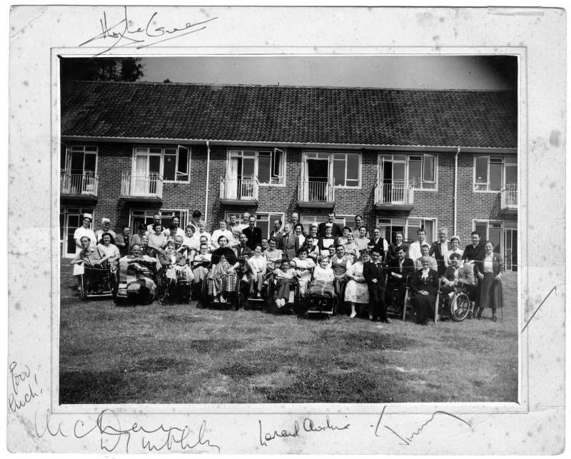 Disabled people and Le Court staff in a posed group on the lawn in front of the new building