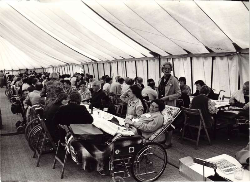Lots of people, some in wheelchairs, sat at long tables inside a marquee