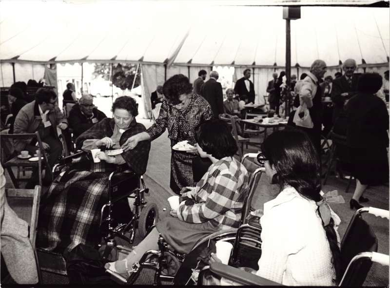 Two women in wheelchairs inside a marquee being offered sandwiches by another woman