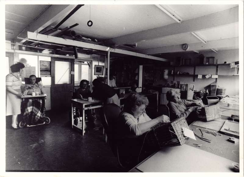 Several people in a workroom setting undertaking basket weaving and one man receiving a cup of tea