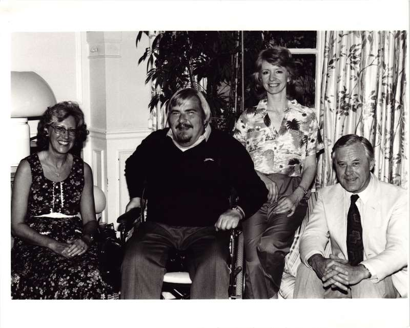 Two men and two women in a posed photo in front of a window. One man in a wheelchair in the centre.