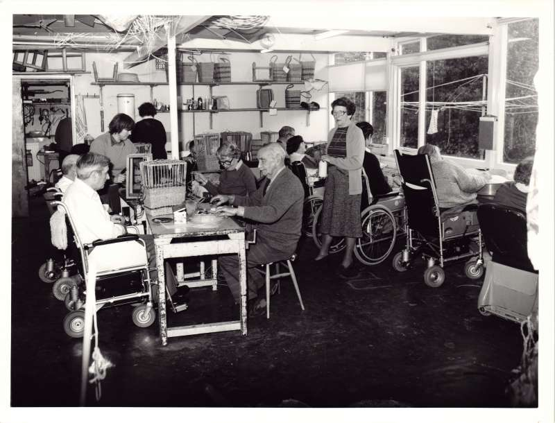 Several people sitting in wheelchairs or on stools in a workshop setting doing various activities