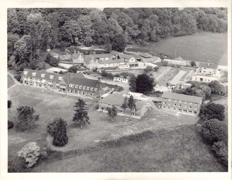 An aerial view of the Le Court Cheshire Home, showing brick buildings and lawns and gardens
