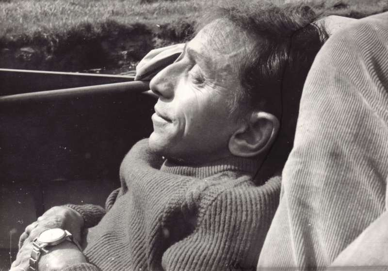 Side-on close-up photograph of a man sitting outside with a cushion behind his back