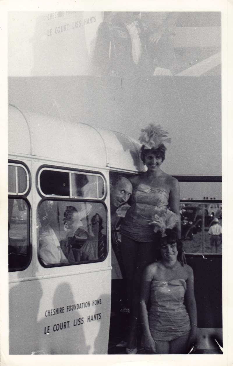 A man poking his head out of a minibus, smiling cheekily at two women dressed in swimsuits