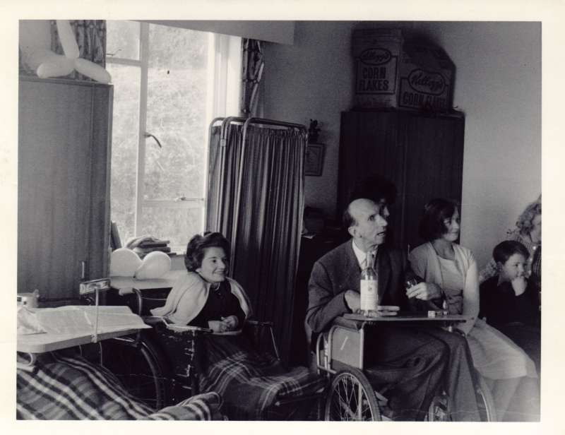 Two women and a man in wheelchairs in a large bedroom with a wardrobe in the background