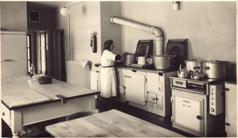 A woman in white overalls stirring a large cooking pot in the kitchens at Le Court