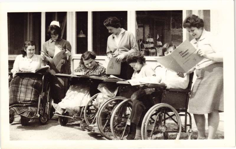 3 women standing and 4 in wheelchairs outside all looking at a booklet called 'The Cheshire Homes'