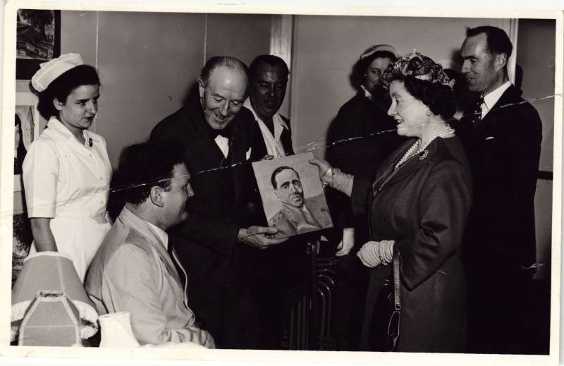 A man in a wheelchair presenting a painting of Leonard Cheshire to HM the Queen Mother whilst others watch on