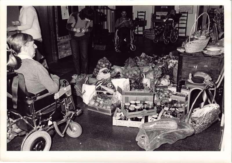 A man in a wheelchair in a hallway looking at pots of jam and fruit and vegetables gathered for a harvest festival.