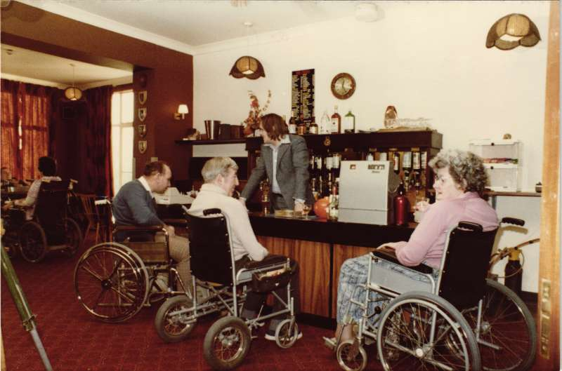 2 men and a woman in wheelchairs holding drinks in front of the bar, with a man serving them