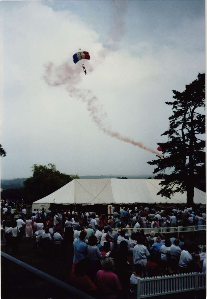 People standing outside a fete marquee looking up into the sky at a parachute jump coming in to land
