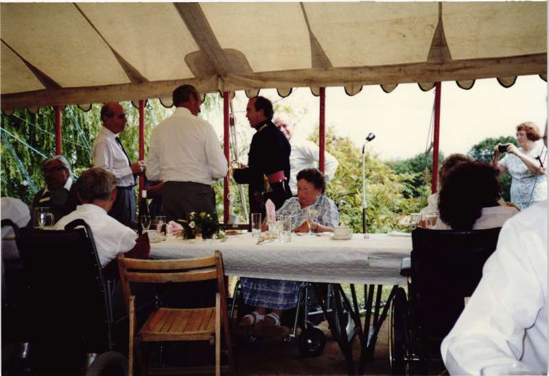 Several people in wheelchairs at a table inside a marquee, with Leonard Cheshire standing talking to two men
